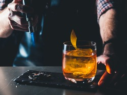 Bright orange Old Fashioned Cocktail with whiskey on a black board. Decorated with burning coal with the smoke. Bartender hand burning the cocktail decoration. Perfect Serve example. Horizontal