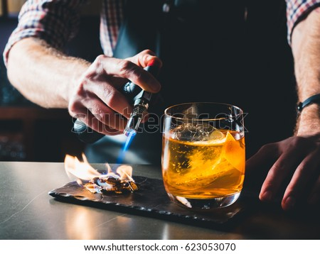 Bright orange Old Fashioned Cocktail with whiskey on a black board. Decorated with burning coal, beautiful flame. Bartender hand burning the cocktail decoration. Perfect Serve example. Horizontal