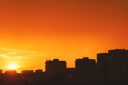 Bright orange sunset over the evening city. Bright lights of tall buildings of urban buildings. Great disk of the rising sun. Sun rays