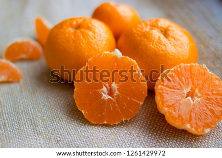 Bright orange tangerines (clementines) whole and peeled with the rind on a burlap  background.Mandarin or clementine oranges, dark still life on rustic hessian. Light painting technique.  #1261429972