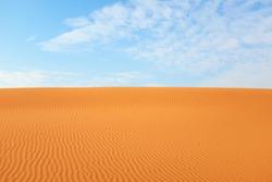 Bright orange textured desert sand and clear bright blue sky for a warm desert summer background
