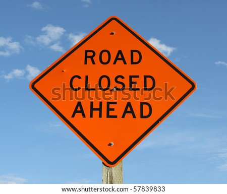 Bright orange warning sign stating the road is closed ahead