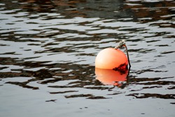 Bright orange water buoy with old rope attached to the top, floating on calm reflective water with ripples and reflections.