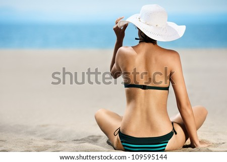 Bright photo of a beautiful model relaxing on a beach. Room for text