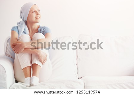 Bright photo of happy pretty girl suffering from kidney cancer, wearing blue headscarf and siting on the couch at hospice after chemotherapy