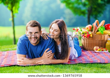 Bright photo of young happy smiling couple in love, lying together on a picnic blanket, outdoors Stok fotoğraf ©