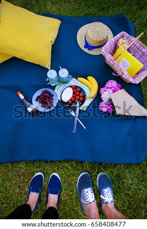 Bright picnic on the nature-flowers, delicious food, a loving couple