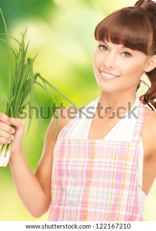 bright picture of beautiful housewife with spring onions over green.