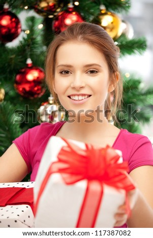bright picture of happy woman with gift box and christmas tree......