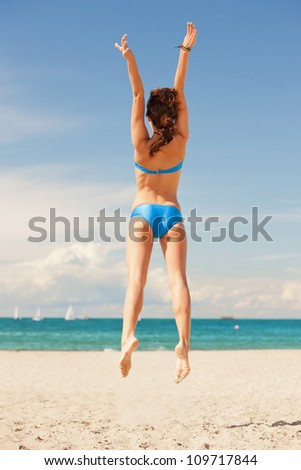 bright picture of jumping woman on the beach.