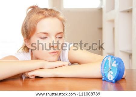 bright picture of pensive teenage girl with clock