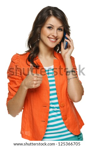 Bright picture of young woman talking on cellphone showing thumb up sign, over white background