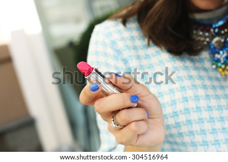 Bright pink lipstick in the hands of the girl. Lipstick in her hands. Cosmetics. Stylish girl in a dress and necklace. Necklace with rhinestones. Brown-haired woman with lipstick. Lipstick.
