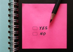 Bright pink note on black notebook page with text handwriiten YES and NO with checkbox , concept of decision making to say yes or say no