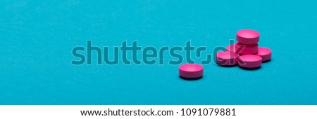 Bright pink pills on dark blue coloured background. Medication and prescription pills web banner with copy space.
