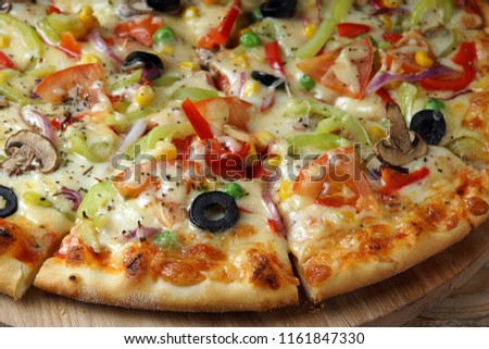 Bright pizza, cut into pieces, with vegetables and mushrooms