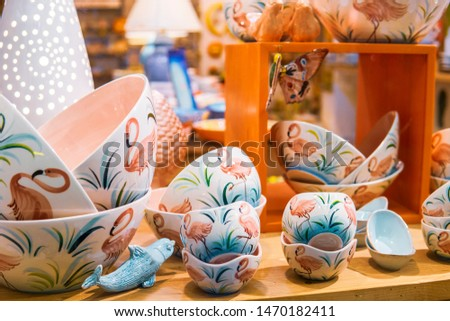 Bright porcelain dishes are on shelves on windowsill in Good for Home shop. Household concept. Design tableware. Pottery template