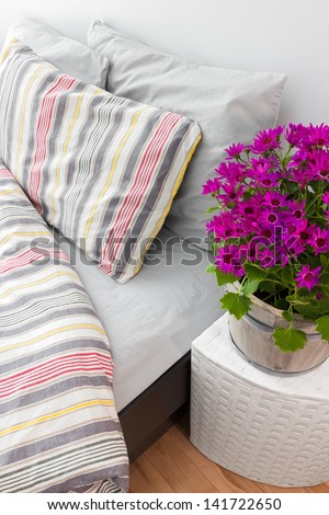 Bright purple flowers decorating a modern bedroom with striped bed linen.