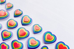 Bright rainbow hearts on white wood board, pattern, border, top view.