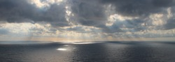 Bright rays of the sun through dramatic dark clouds over the sea, spots of light on the water, wide view.