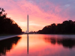 Bright red and orange sunrise at dawn reflects Washington Monument in new reflecting pool by Lincoln Memorial