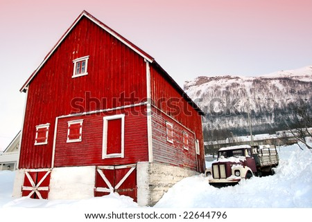 Bright red barn and old brown truck against white snow