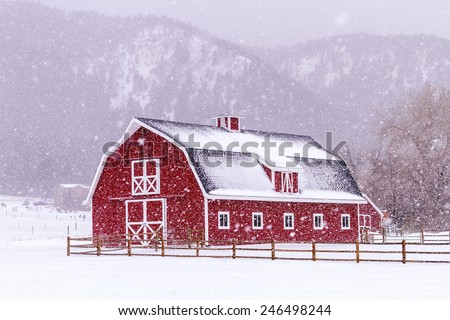 Bright red barn covered with snow surrounded with wooden fence on snowy winter day