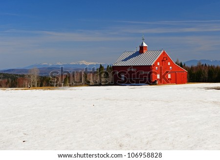 Bright red barn on a field of snow with the white mountains off in the distance.