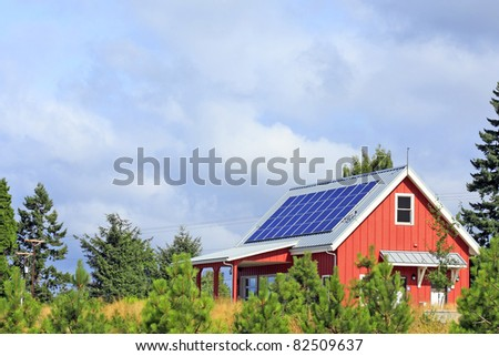 Bright red building with solar panels on the metal rooftop on a mostly sunny summer day in a public park.