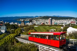 Bright red cable car going down the hill on a sunny day. Wellington, New Zealand