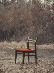 Bright red chair (Vertical). A bright red chair outside. Discarded furniture, old stuff. A chair from the trash can. Alone in the background of the forest. Bright red.