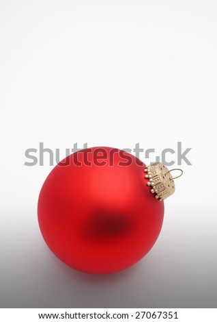 bright red christmas tree ornament bulb on white and gray background isolated with room above for text