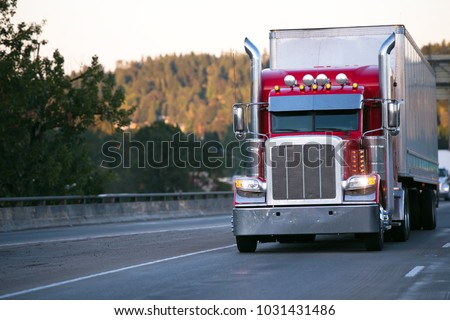 Bright red classic big rig semi truck with high exhaust pipes and chrome accessories transporting goods in dry van trailer move on evening road with turn on headlight