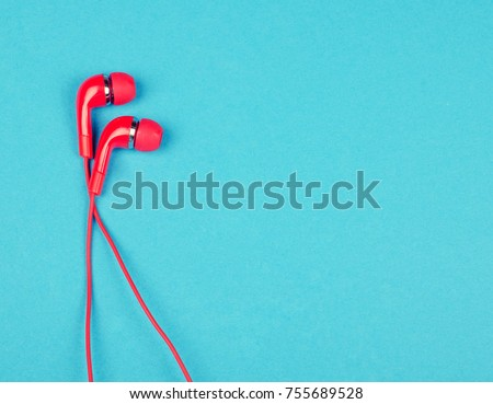 Bright red earbud headphones isolated on a bright blue background with copy space on the right for your text (minimal concept, top view) #755689528