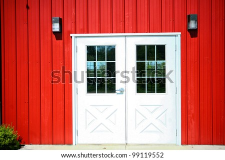 Bright red farmhouse facade with white barn doors