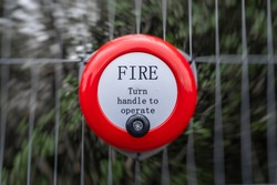 Bright red fire alarm bell turn handle spin around to operate alert manual steel ringing on construction building site attached to metal fence