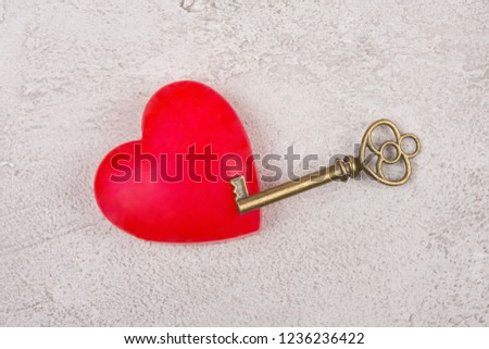 Bright red heart and an old antique key on a gray marble or concrete background (top view) as the Valentine day or love concept #1236236422