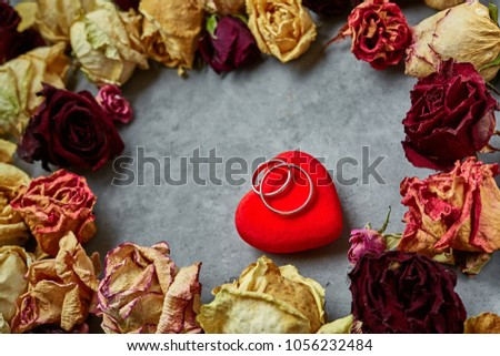 bright red heart and wedding rings on the dark gray concrete background in frame from dried roses #1056232484