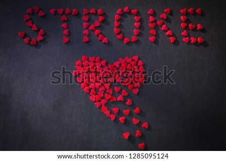 Bright red heart consists of small pieces. Inscription Stroke from small hearts. Dark background, top view. #1285095124