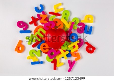 Bright red heart in the middle of brightly coloured plastic letters and numbers on a white background #1257123499