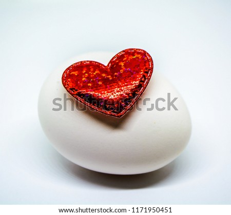 Bright red heart lying on a chicken egg #1171950451