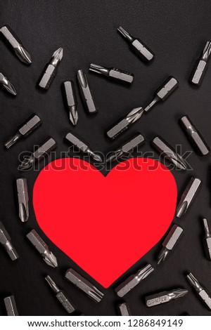 Bright red heart on a black background with various nozzles for a screwdriver. #1286849149