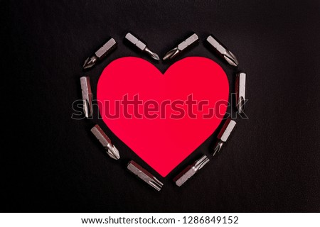Bright red heart on a black background with various nozzles for a screwdriver. #1286849152