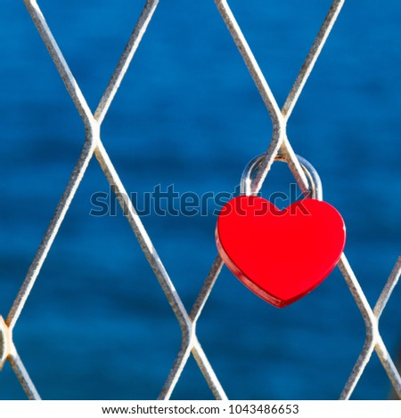 Bright red heart padlock on a chain link fence at the beach. #1043486653