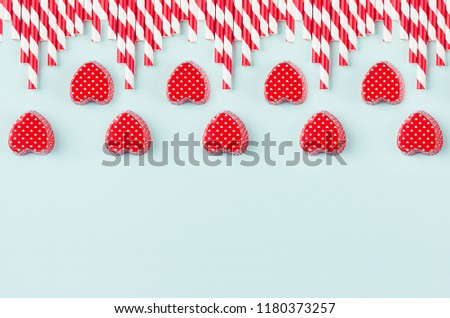 Bright red hearts and cocktail straws as decorative border on mint pastel paper background. Valentine's day youth design concept art. #1180373257