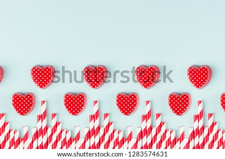 Bright red hearts and cocktail straws as decorative border on mint pastel paper background. Valentine's day youth design concept art. #1283574631