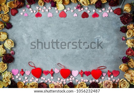 bright red hearts on the dark gray concrete background in frame from dried roses #1056232487