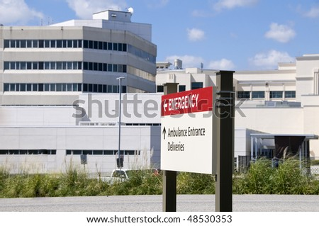Bright red hospital Emergency entrance sign in front of a hospital building