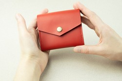 bright red leather wallet in female hands close-up on a gray background