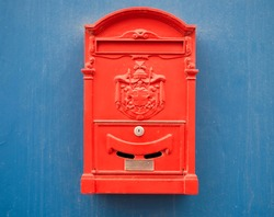 Bright red mail box on a blue background.